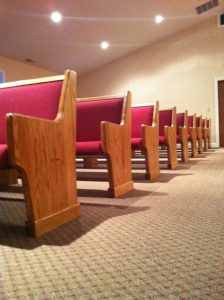 rows of church pews with red cushion