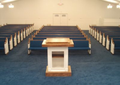 rows of church pews with blue cushions