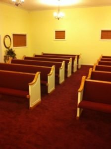 rows of pews with red fabric