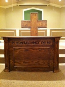 """wooden cross pulpit and """"in remembrance of me"""" table"""