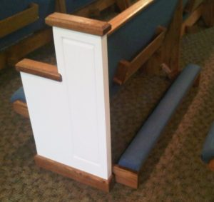 white church pew with blue cushioned kneeler