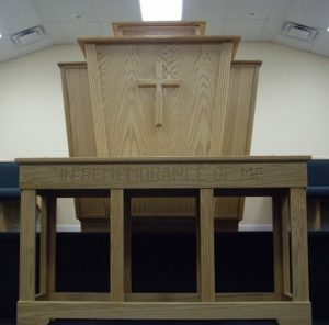 """in remembrance of me"" table and pulpit with cross"