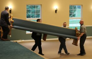 four men carrying a pew