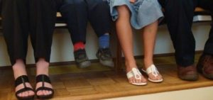kid with mismatched socks sitting by adults as his feet are dangling.