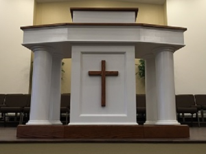 white pulpit with wood cross and details