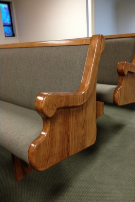 Wooden church pews with grey upholstery