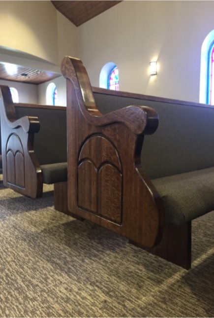 Dark wood engraved church pew ends